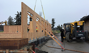 Cross Laminated Timber wall panel placed in a construction project with pre-cut spaces for doors and windows