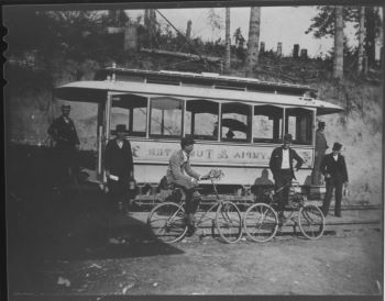 A historic photo of a trolley and people on bicycles in Tumwater.
